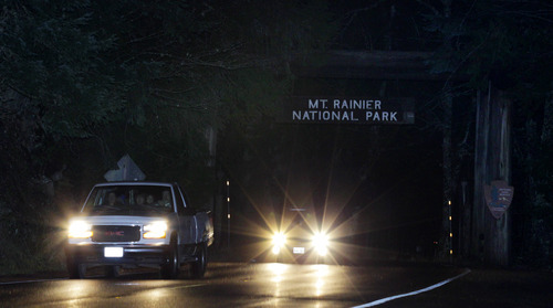 A convoy of evacuees leaves Mount Rainier National Park in the early morning hours of Monday, Jan. 2, 2012 in Washington state. More than 100 people were kept in guarded conditions at a visitors center in the park until the evacuation as a safety precaution after a gunman shot and killed a park ranger during a traffic stop, fled on foot, and remained at-large overnight. (AP Photo/Ted S. Warren)