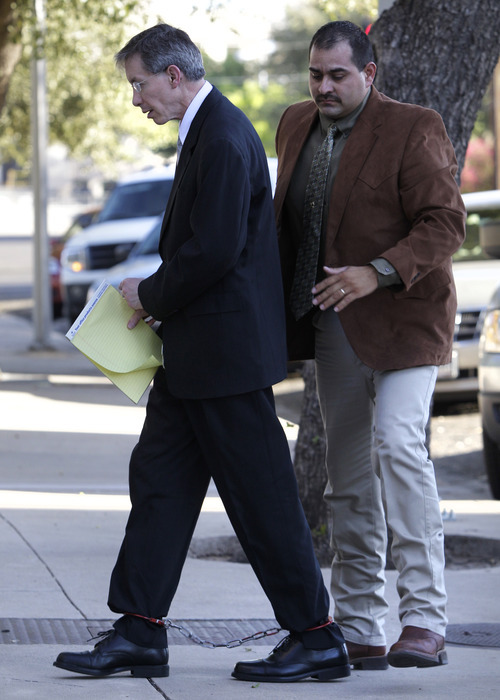 A law enforcement officer, right, assist Polygamist religious leader Warren Jeffs, left, as he arrives in wrist and leg shackles to the Tom Green County Courthouse for the sentencing phase of his sexual assault trial Friday Aug. 5, 2011, in San Angelo, Texas.  (AP Photo/Tony Gutierrez)