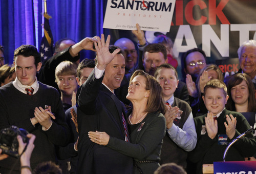 Republican presidential candidate, former Pennsylvania Sen. Rick Santorum is joined by his wife Karen as he waves to supporters at his Iowa caucus victory party Tuesday, Jan. 3, 2012, in Johnston, Iowa. (AP Photo/Charlie Riedel)