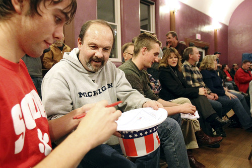 Jay Tessmer, of Clermont, Iowa, second from left, hands the hat to his son, Jacob Tessmer, 18, to deposit his ballot during the Republican caucus for Clermont and Pleasant Valley / Elgin precincts at the Clermont Opera House on Tuesday, Jan. 3, 2011, in Clermont. (AP Photo/The Gazette, Liz Martin)