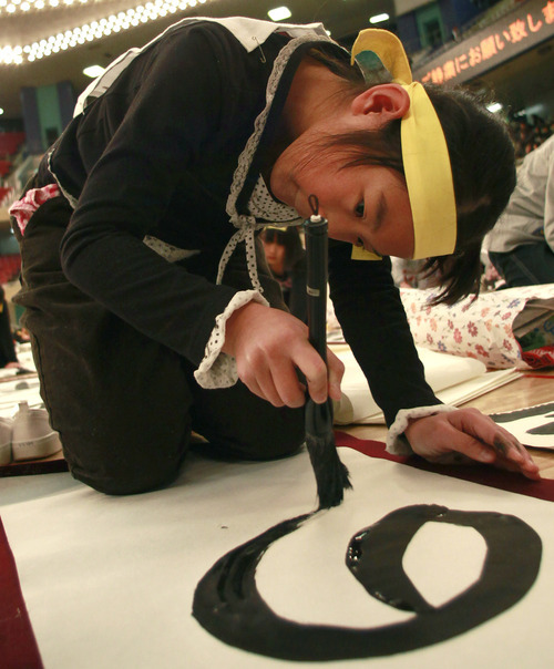 A girl uses a large brush to show her Japanese calligraphy skill on her way to inking