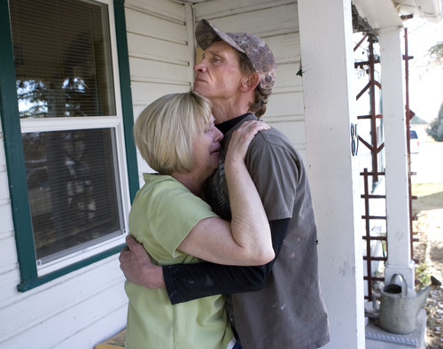 Al Hartmann     The Salt Lake Tribune Denise Atwood cries Tuesday as her husband, Mike, holds her on the front porch of their Fairview home after hearing that their daughter, Angela Atwood, was captured in Nevada. Angela Atwood is one of the two suspects of a crime spree that claimed the lives of a Mount Pleasant couple and left a woman seriously injured.
