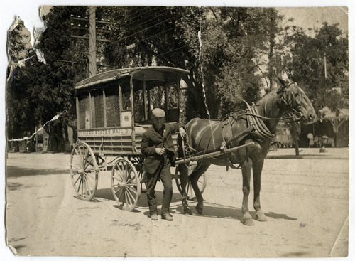 Tribune file photo  A man stands with a U.S. Mail wagon in this undated photo.