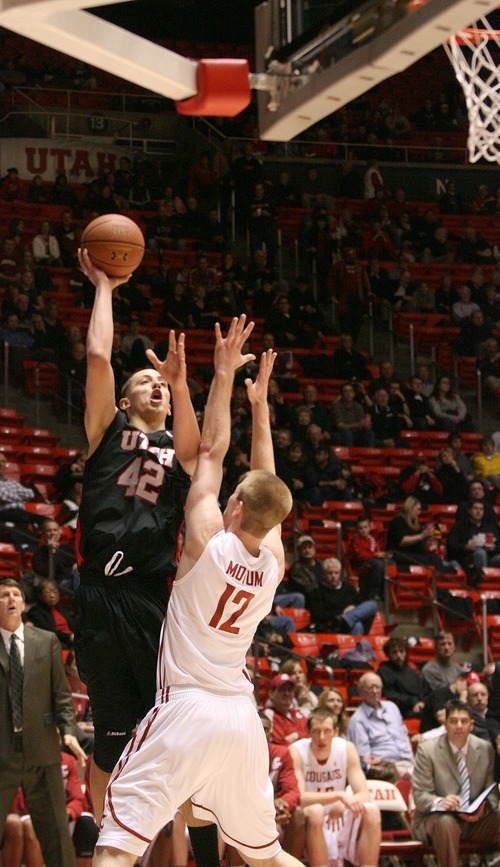 Paul Fraughton | The Salt Lake Tribune. Utah's Jason Wasburn takes the shot over Washington State's Brock Motum .Utah played Washington State in the Huntsman Center.  Thursday, January 5, 2012