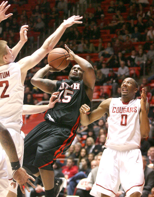 Paul Fraughton | The Salt Lake Tribune. Utah's Josh Watkins puts the ball up against Washington State defenders  Brock Motum and Marcus Capers. Utah played Washington State in the Huntsman Center.  Thursday, January 5, 2012