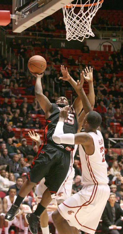 Paul Fraughton | The Salt Lake Tribune. Utah's Josh Watkins  drives to the basket as Washington State's  D.J. Shelton defends. Utah played Washington State in the Huntsman Center.  Thursday, January 5, 2012