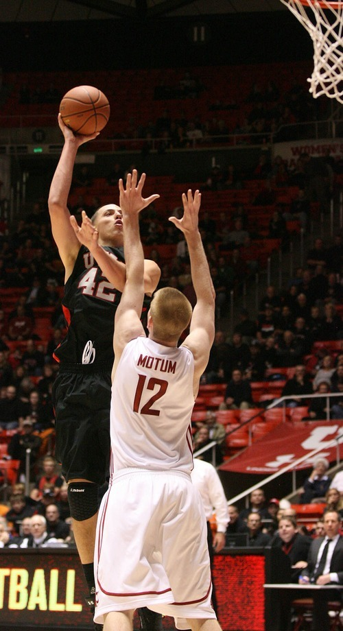 Paul Fraughton | The Salt Lake Tribune.  In the overtime period Jason Washburn shoots the ball over Washington State's Brock Motum. Utah played Washington State in the Huntsman Center.  Thursday, January 5, 2012