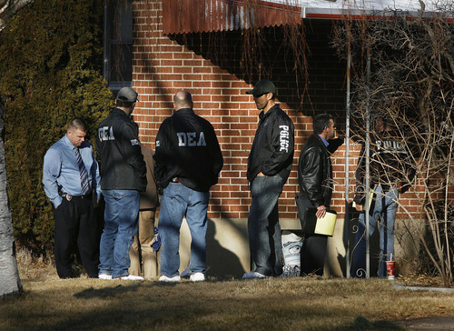 Scott Sommerdorf     The Salt Lake Tribune              DEA and police officers stand outside the home at 3268 Jackson St. in Ogden, Thursday, Jan. 5, 2012. Five police officers were injured and one killed in a firefight during a drug raid Wednesday night.