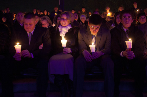 Relatives of Jared Francom from left, brother Travis Francom, Travis' wife Jessica Francom, and brothers Ben Francom and Gunner Francom, attend a candle light vigil for law enforcement officers shot the night before, Thursday, Jan. 5, 2012, in Ogden. Six area law enforcement officers were shot Wednesday night while serving a search warrant. Jared Francom died from his wounds. (AP Photo/Jim Urquhart)
