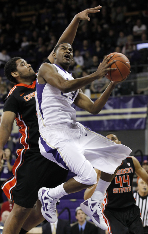 Washington's C.J. Wilcox, right, gets a shot off in front of Oregon State's Joe Burton in the first half of an NCAA college basketball game Thursday, Dec. 29, 2011, in Seattle. (AP Photo/Elaine Thompson)