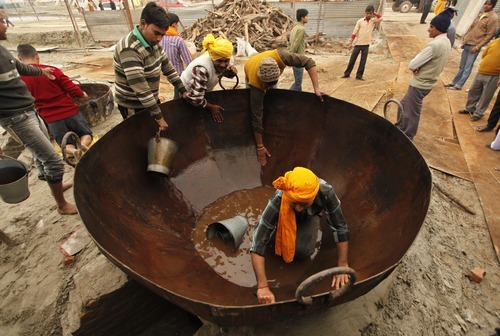 Hindu devotees wash a huge iron cooking pot at Sangam, the confluence of the rivers Ganges and Yamuna, during the annual Hindu religious fair of Magh Mela in Allahabad, India, Sunday, Jan. 8, 2012. The Magh Mela, which began Sunday, involves bathing on auspicious dates spread over a period of 45 days at the confluence considered holy by Hindus. (AP Photo/Rajesh Kumar Singh)