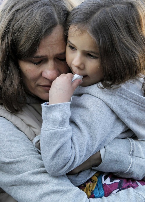 Ina Menzl, left, hugs her daughter, 4-year-old Rebecca Kraft, Sunday, Jan. 8, 2012, in Tucson, Ariz., outside the Safeway grocery store where U.S. Rep. Gabrielle Giffords, D-Ariz., was shot one year ago during a shooting spree that left 6 dead and 13 wounded, including Giffords. (AP Photo/Matt York)