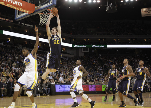 Utah Jazz's Gordon Hayward (20) lays up a shot over Golden State Warriors' Dorell Wright, left, and Nate Robinson (2) during the first half of an NBA basketball game Saturday, Jan. 7, 2012, in Oakland, Calif. (AP Photo/Ben Margot)