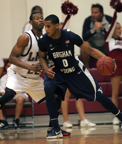 BYU's Brandon Davies (0) dribbles against Loyola Marymount's Godwin Okonji (22) during an NCAA college basketball game, Thursday, Jan. 5, 2012, in Los Angeles. BYU won 73-65. (AP Photo/Ringo H.W. Chiu)