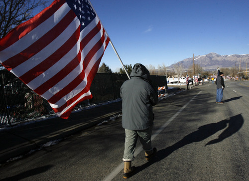 Francisco Kjolseth  |  The Salt Lake Tribune Dan Wardell of South Ogden carries the American flag as he joins thousands who turned up to pay their respects for slain Ogden police Officer Jared Francom along the funeral procession route in Ogden on Wednesday, January 11, 2012.