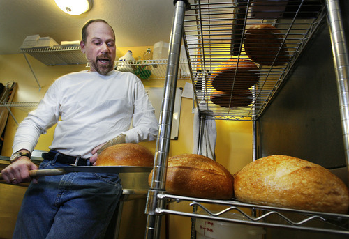 Scott Sommerdorf  |  The Salt Lake Tribune              Chris Stokes, chef and owner of the Happy Harbor Bread Co. in Bountiful, checks one of his finished rounds of sourdough in his home commercial kitchen.