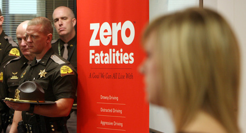 Steve Griffin  |  The Salt Lake Tribune Ashli Hendricks, right, is joined by Utah Highway Patrol troopers as she talks about her father's death in a car accident in which he was not wearing a seat belt. In 2011, 233 people died on Utah roads.