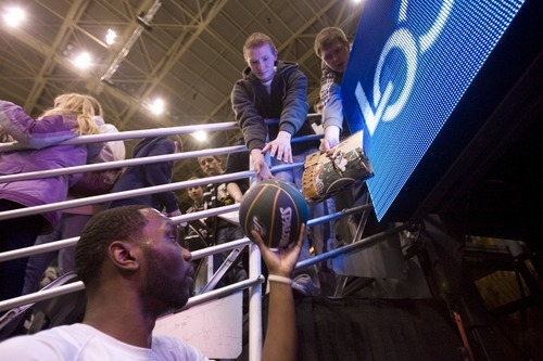 Kim Raff  | The Salt Lake Tribune Jazz player Al Jefferson signs autographs during pre-game warmup at EnergySolutions Arena in Salt Lake City on Saturday.