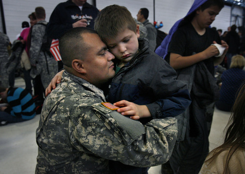 Scott Sommerdorf     The Salt Lake Tribune              Elijah Sandoval nervously touches the flag insignia on his father's uniform as he says a long farewell to Cpl. Alberto Sandoval as the soldiers of the Utah Army National Guard's First Battalion, 211th Aviation leave on the first leg of their 12-month deployment to Afghanistan, Monday January 16, 2012.