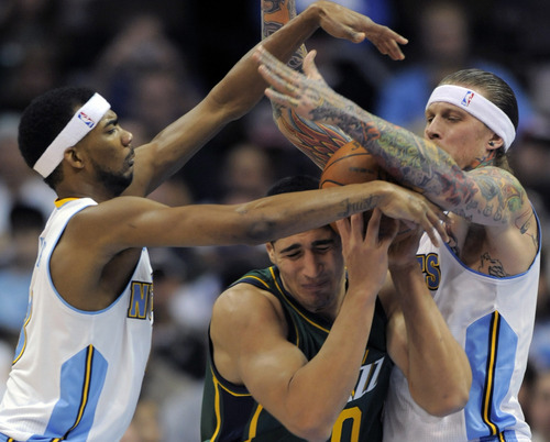 Jack Dempsey  |  The Associated Press Utah Jazz forward Enes Kanter (0) looses possession of the ball while being pressured by Denver Nuggets guard Corey Brewer (13) and Chris Andersen, right, during the second quarter of an NBA basketball game Sunday in Denver. The Jazz won, 106-96.