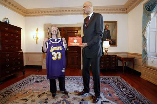 Secretary of State Hillary Rodham Clinton laughs after receiving a Los Angeles Lakers basketball jersey as a gift from global cultural ambassador and former NBA basketball star Kareem Abdul-Jabbar, Wednesday, Jan. 18, 2012, at the State Department in Washington. Abdul-Jabbar will travel the world to engage a generation of young people to help promote diplomacy.   (AP Photo/Jacquelyn Martin)