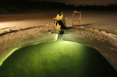 Orthodox priest conducts a service at the ice hole of a lake on the eve of Russian Orthodox Epiphany in Minsk, Belarus, late Wednesday, Jan. 18, 2012. Orthodox Church believers celebrate Epiphany on Jan. 19. (AP Photo/Sergei Grits)