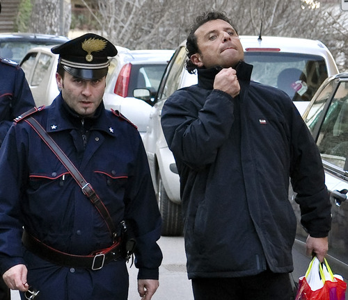 In this photo taken on Saturday, Jan. 14, 2012, and made available Wednesday, Jan. 18, 2012, Francesco Schettino, right, the captain of the luxury cruise ship Costa Concordia, which ran aground Friday off the tiny Tuscan island of Isola del Giglio, is taken into custody by Carabinieri in Porto Santo Stefano, Italy. Schettino, released on Tuesday, and currently under house arrest in his hometown of Meta di Sorrento, southern Italy, is being investigated for possible manslaughter charges and abandoning the ship. (AP Photo/Giacomo Aprili)