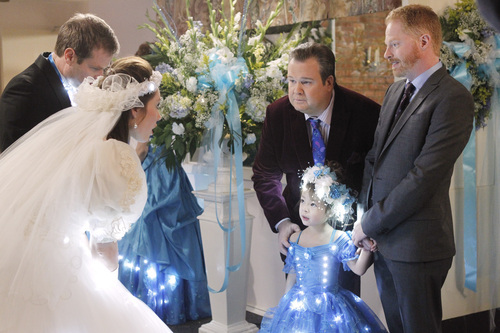 Jesse Tyler Ferguson as Mitchell Pritchett, and Eric Stonestreet as Cameron Tucker are shown with Aubrey Anderson-Emmons, who plays their adopted daughter, Lily, in a scene from