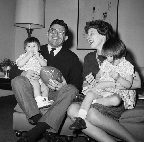 Joe Paterno, new head football coach at Penn State, left, poses with his two-year-old daughter Diana Lynne Paterno, right on mothers lap, his wife Suzanne Paterno and their one-year-old daughter Mary Kathryn Paterno, on fathers lap, in his home following the announcement, Feb. 19, 1966, University Park, Pa. (AP Photo/Paul Vathis)