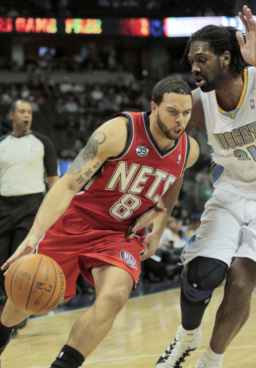 New Jersey Nets point guard Deron Williams (8) drives past Denver Nuggets center Nene Hilario (31) during the first quarter of an NBA basketball game, Wednesday, Jan. 11, 2012 in Denver.  (AP Photo/Barry Gutierrez)