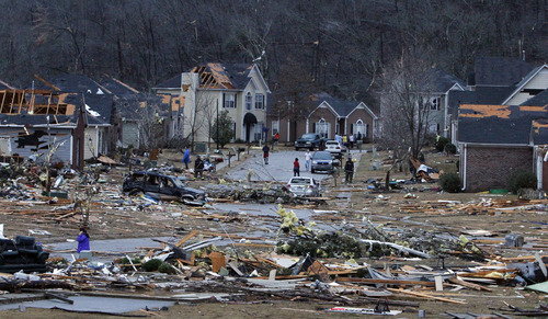 Residents walk around through the debris of their neighborhood after a severe storm ripped through the Trussville, Ala., area in the early hours of Monday, Jan. 23, 2012. Jefferson County sheriff's spokesman Randy Christian said the storm produced a possible tornado that moved across northern Jefferson County around 3:30 a.m., causing damage in Oak Grove, Graysville, Fultondale, Center Point, Clay and Trussville. (AP Photo/Butch Dill)