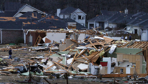 Residents walk around through the debris of their neighborhood after a tornado ripped through the Trussville, Ala. area in the early hours of Monday, Jan. 23, 2012. Jefferson County sheriff's spokesman Randy Christian said the storm produced a possible tornado that moved across northern Jefferson County around 3:30 a.m., causing damage in Oak Grove, Graysville, Fultondale, Center Point, Clay and Trussville. (AP Photo/Butch Dill)