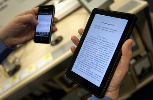 Amazon's Kindle Fire tablet computer, right, is displayed with an Apple iPhone 4. Scott Eells  |  Bloomberg