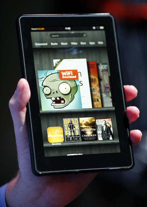 An Amazon.com employee displays the company's new Kindle Fire tablet computer. Amazon, the world's largest online retailer, is taking aim at Apple's best-selling iPad with a device that's smaller and less than half the price. Emile Wamsteker  |  Bloomberg