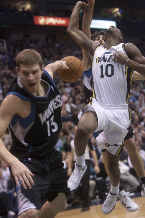 Jeremy Harmon  |  The Salt Lake Tribune  Minnesota's Luke Ridnour falls out of bounds after colliding with Alec Burks as the Jazz host the Timberwolves at EnergySolutions Arena Saturday, Jan. 21, 2012 in Salt Lake City.