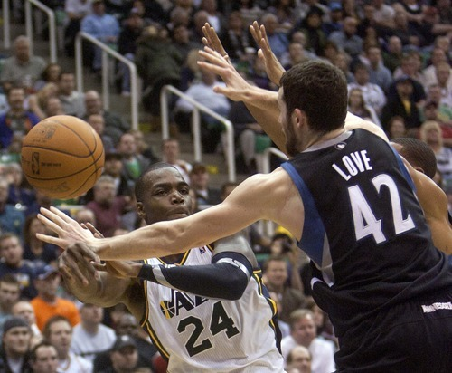 Jeremy Harmon  |  The Salt Lake Tribune  Paul Millsap passes the ball around Minnesota's Kevin Love and Wes Johnson as the Jazz host the Timberwolves at EnergySolutions Arena Saturday, Jan. 21, 2012 in Salt Lake City.