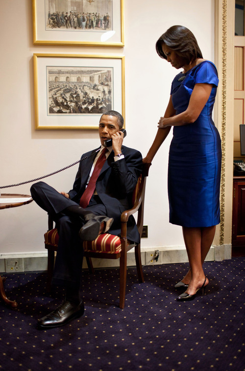 This handout photo provided by the White House shows President Barack Obama, accompanied by first lady Michelle Obama, during a phone call from the Capitol in Washington, Tuesday, Jan. 24, 2012, immediately after his State of the Union Address, informing John Buchanan that his daughter Jessica was rescued by U.S. Special Operations Forces in Somalia. (AP Photo/Pete Souza, White House)