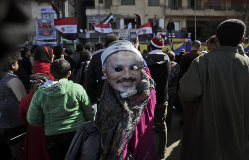An Egyptian woman wearing a mask depicting Emad Effat, a Muslim cleric killed during clashes with security forces, takes part in a rally to mark the first anniversary of