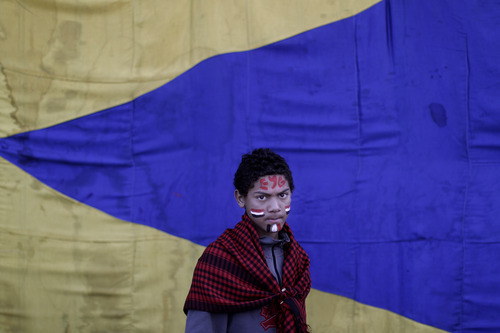 Egyptian protestor Khalid Ali, 14, his face painted in the colors of his national flag, attends a rally to mark the first anniversary of the