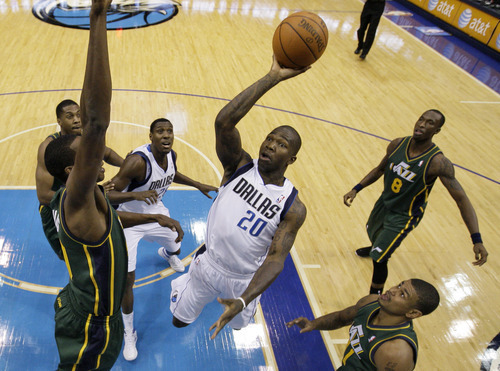 Dallas Mavericks shooting guard Dominique Jones (20) goes up for a shot as Utah Jazz's Devin Harris left, defends in the first half of an NBA basketball game on Friday, Jan. 27, 2012, in Dallas. Jazz's Earl Watson, bottom, and Josh Howard (8) look on. (AP Photo/Tony Gutierrez)