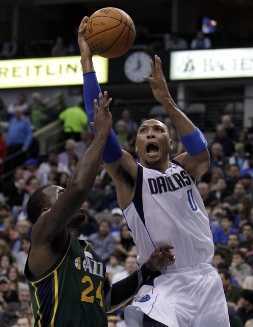 Dallas Mavericks' Shawn Marion (0) goes up for a shot over Utah Jazz's Paul Millsap (24) in the first half of an NBA basketball game on Friday, Jan. 27, 2012, in Dallas. (AP Photo/Tony Gutierrez)