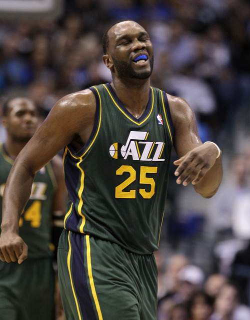 Utah Jazz center Al Jefferson (25) reacts to being charged with a foul in the first half of an NBA basketball game against the Dallas Mavericks, Friday, Jan. 27, 2012, in Dallas. The Mavericks won 116-101. (AP Photo/Tony Gutierrez)