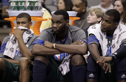 From left to right, Utah Jazz's Earl Watson, Al Jefferson and Paul Millsap sit on the bench in the final minutes of the second half of an NBA basketball game against the Dallas Mavericks, Friday, Jan. 27, 2012, in Dallas. The Mavericks won 116-101. (AP Photo/Tony Gutierrez)
