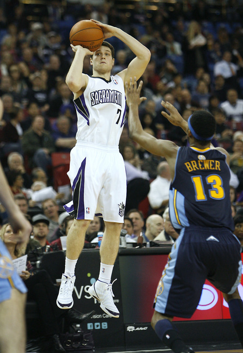 Sacramento Kings guard Jimmer Fredette (7) shoots in front of Denver Nuggets defender Corey Brewer (13) during the second half of an NBA basketball game in Sacramento, Calif., on Wednesday, Jan. 25, 2012.  The Nuggets won 122-93.(AP Photo/Steve Yeater)
