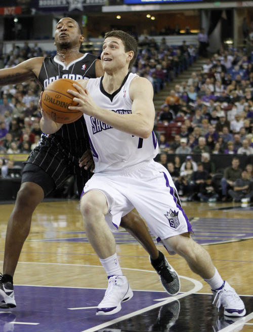 In this photo taken Sunday, Jan. 8, 2012, Sacramento Kings guard Jimmer Fredette, right, drives to the basket against Orlando Magic guard Chris Duhon during an an NBA basketball game against the Orlando Magic in Sacramento, Calif. (AP Photo/Rich Pedroncelli)