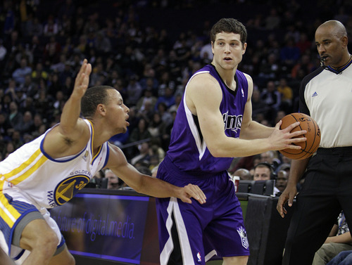 Sacramento Kings' Jimmer Fredette looks to pass away from Golden State Warriors' Stephen Curry during an NBA basketball preseason game, Saturday, Dec. 17, 2011, in Oakland, Calif. (AP Photo/Ben Margot)