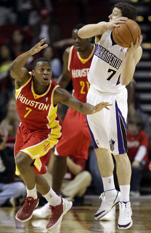 Houston Rockets' Kyle Lowry, left, tries to steal the ball from Sacramento Kings' Jimmer Fredette, right, during the third quarter of an NBA basketball game Friday, Jan. 13, 2012, in Houston. The Rockets defeated the Kings 103-89. (AP Photo/David J. Phillip)