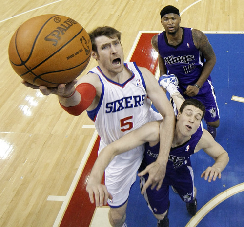 Philadelphia 76ers' Andres Nocioni (5), of Argentina, goes up for a shot as Sacramento Kings' Jimmer Fredette, right front, and DeMarcus Cousins defend in the second half of an NBA basketball game Tuesday, Jan. 10, 2012, in Philadelphia. Philadelphia won 112-85. (AP Photo/Matt Slocum)