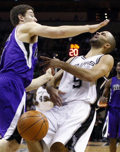 San Antonio Spurs' Tony Parker, (9), of France, is fouled by Sacramento Kings' Jimmer Fredette, left, during the second quarter of an NBA basketball game on Friday, Jan. 20, 2012, in San Antonio. (AP Photo/Eric Gay)