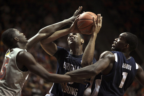 BYU's Brandon Davies (0) center, is fouled by Virginia Tech's Dorian Finney-Smith (15),left, after an offensive rebound with BYU's Charles Abouo (1), right, during first-half NCAA college basketball game action in Blacksburg, Va., Wednesday, Jan. 25 2012. (AP Photo/The Roanoke Times, Matt Gentry)